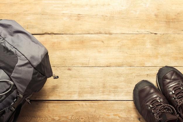 Mochila de senderismo y botas sobre superficie de madera. el concepto de senderismo en las montañas o el bosque, turismo, tienda de campaña, campamento. vista plana, vista superior.