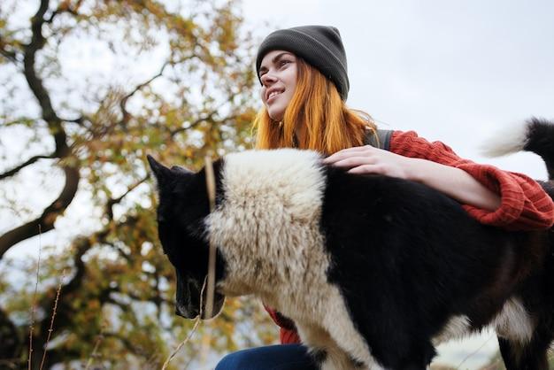 Mochila de turista mujer jugando con amistad de viaje de perro