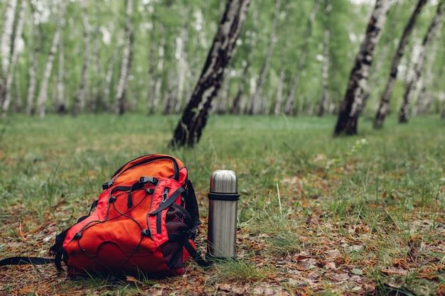 Mochila turística, termo con té en bosque de primavera. viajar.