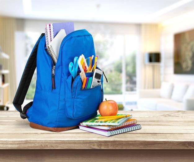 Mochila con útiles escolares en la mesa sobre el interior educativo borroso