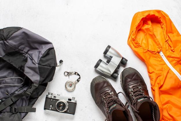 Mochila de viaje, brújula, botas, chaqueta, cámara y binoculares sobre un fondo blanco. caminata conceptual, turismo, campamento. vista plana, vista superior