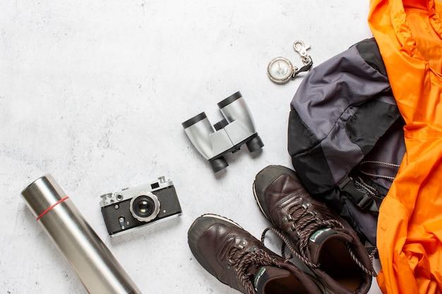 Mochila de viaje, brújula, botas, termo, chaqueta, cámara y binoculares sobre un fondo blanco. concepto de senderismo, turismo, campamento, montañas, bosque.