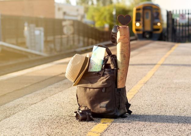 Mochila de viaje verde, gorro, mapas, gafas en el andén de la estación de tren y tren al atardecer