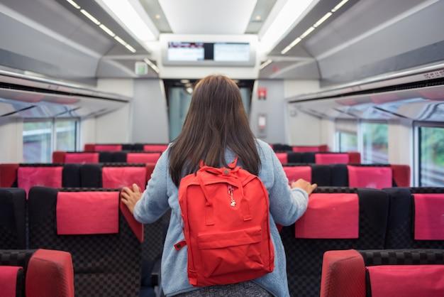 Mochila de viajero mujer de pie en el tren de la velocidad.