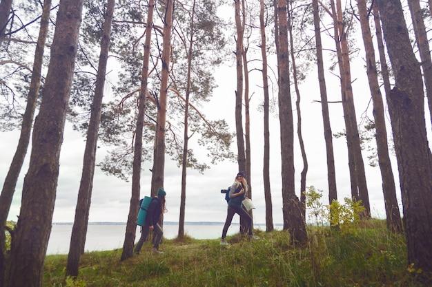 Mochila viajeros jóvenes en el lago del bosque