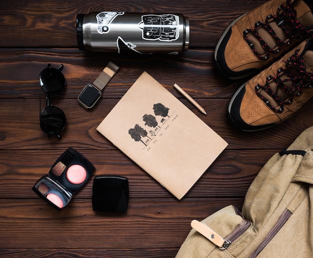 Mochila, zapatillas, termo, reloj, bloc de notas sobre un fondo de madera. accesorios de viaje para mujer sobre un fondo de madera. kit de viajera femenina.
