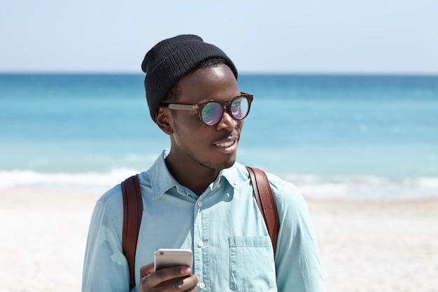 Mochilero afroamericano cansado con sombrero y gafas usando la aplicación de servicio de taxi en línea en el teléfono móvil para solicitar un taxi mientras tiene sed, buscando un lugar para tomar un refresco