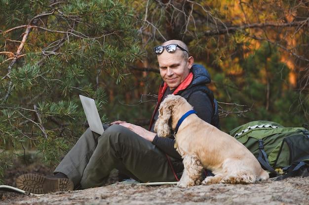 Mochilero de edad avanzada con portátil y perro en el bosque
