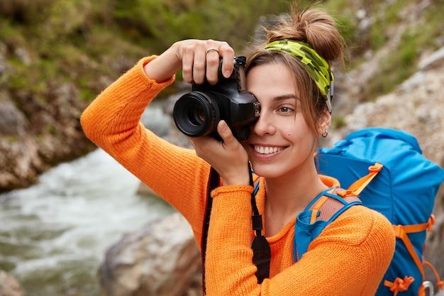 Mochilero feliz posa contra el río de la montaña que fluye a través del bosque verde, hace fotos de paisajes maravillosos