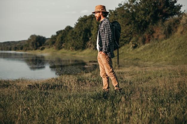 Mochilero hombre hipster tranquilo de pie junto al lago