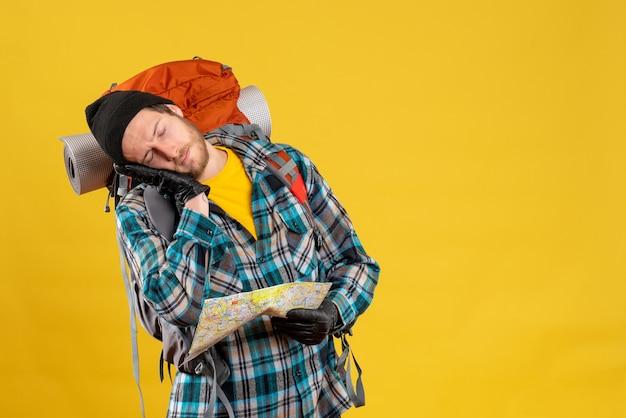 Mochilero joven soñoliento con sombrero negro sosteniendo mapa de viaje