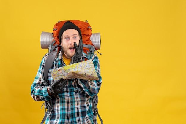 Mochilero joven sorprendido con guantes de cuero sosteniendo mapa de viaje