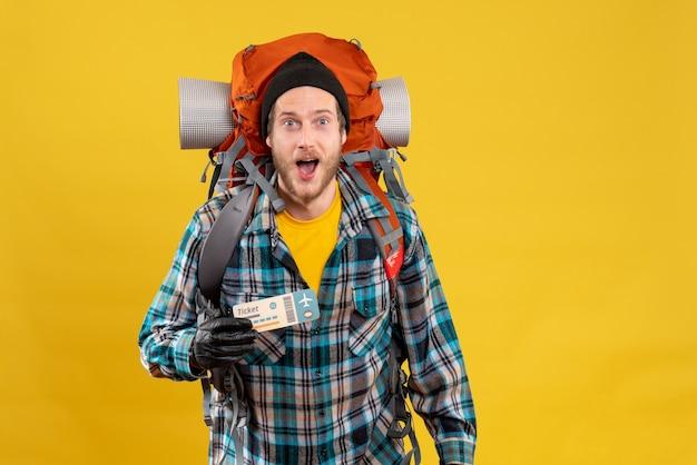 Mochilero joven sorprendido con sombrero negro sosteniendo boleto de viaje