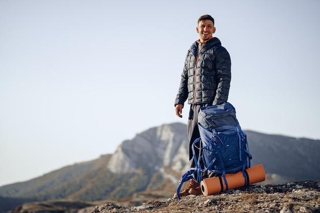 Mochilero masculino en equipo de senderismo de pie en la cima de la montaña