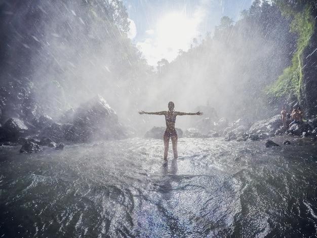 Mochilero de la mujer joven que mira la cascada en selvas. chica de viaje de imagen de concepto de ecoturismo