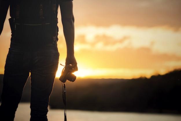 Mochilero relajarse en la montaña con cámara y puesta de sol