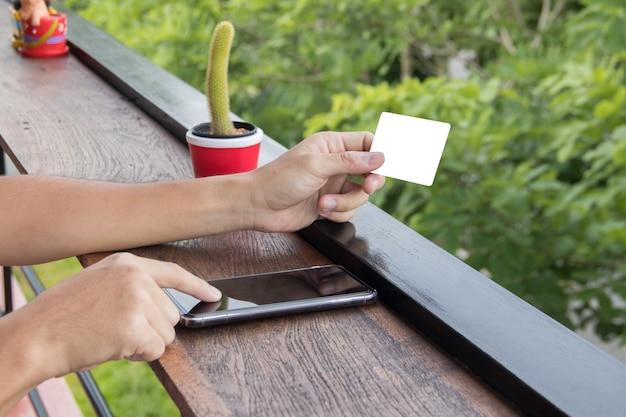 Mock up hold tarjeta de crédito en blanco y toque el teléfono celular