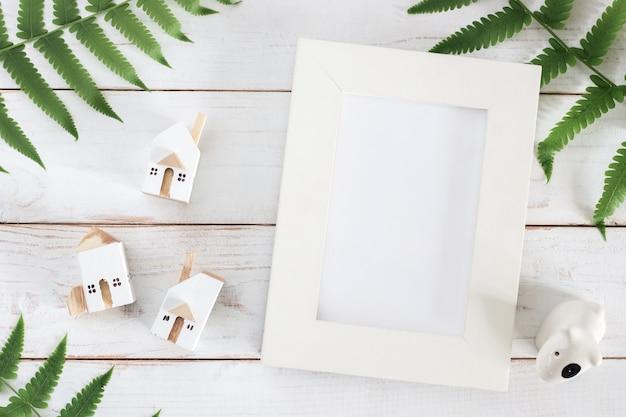 Mock up, marco de fotos en blanco con hoja de helecho y modelo de casa blanca en miniatura sobre fondo blanco de tablones de madera, minimalista