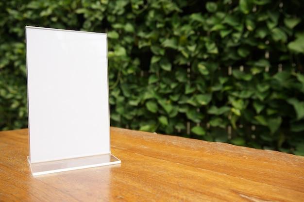Mock up marco de menú de pie en la mesa de madera en el café del restaurante bar. espacio para el texto. montaje de la pantalla del producto