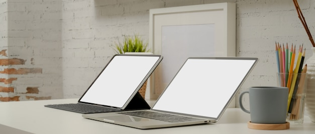 Mock up portátil y tableta digital con teclado en mesa de trabajo moderna con papelería y decoraciones