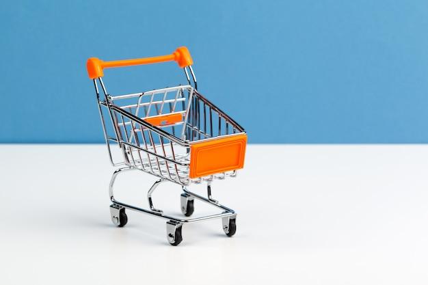 Mock up shoppong carro en línea en la mesa de escritorio de la oficina de pared azul suave