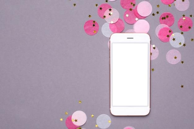 Mock up de teléfono móvil y confeti rosa con estrellas doradas en gris