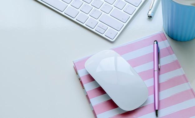 Mockup compute mouse y bolígrafo en el cuaderno con teclado de computadora y taza en la mesa superior blanca.