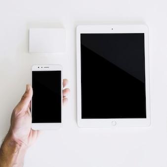 Mockup con mano sujetando smartphone y tablet