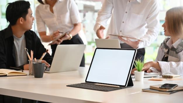 Mockup tablet pc en sala de reuniones con personas reunión, tableta de pantalla vacía.