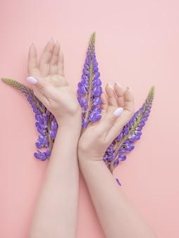 Moda arte mano mujer en verano y flores en sus manos. las muchachas creativas de la mano de la foto de la belleza que se sientan en la tabla con los altramuces azules florecen. concepto de cuidado de la piel