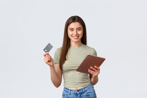Moda y belleza, estilo de vida y concepto de compras, sonriente, apuesto cliente femenino, haciendo pedidos en línea con tarjeta de crédito y tienda de tableta digital en pared blanca de internet