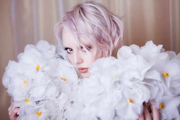 Moda belleza modelo mujer en rosas blancas.