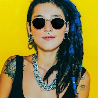 Moda chica guapa con rastas y piercings sobre pared amarilla colorida