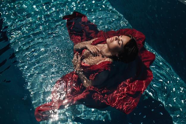Moda: chica con maquillaje brillante en un vestido rojo tumbado en la piscina. mujer joven con los ojos cerrados posando en el agua