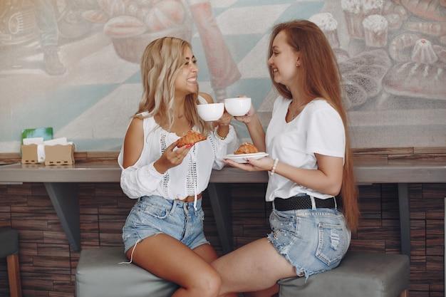 Moda chicas jóvenes sentados en un café