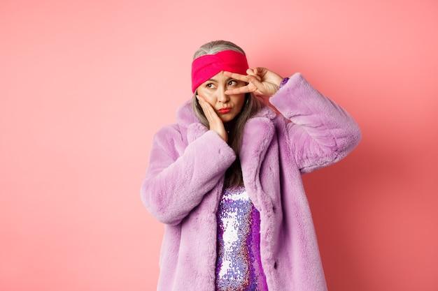Moda y compras. modelo femenino asiático elegante y moderno, mostrando signos de paz y luciendo lindo y tonto, posando en abrigo de piel sintética púrpura sobre fondo rosa