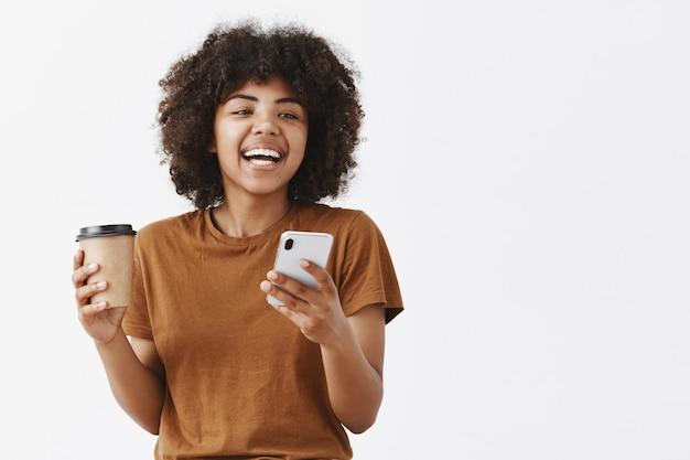 Moda despreocupada chica afroamericana con cabello rizado en camiseta marrón riendo mientras habla con amigos tomando café de una taza de papel y sosteniendo un teléfono inteligente