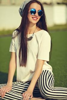 Moda elegante hermosa morena joven modelo en ropa casual de verano hipster posando en el fondo de la calle en el parque