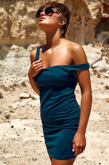 Moda elegante hermosa morena joven modelo en vestido azul de verano posando cerca de rocas de arena