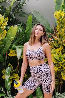 Moda elegante joven caucásica ajuste mujer deportiva en leopardo cami top y pantalones cortos de motociclista fuera tiene coctelera de proteínas