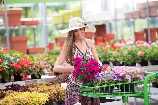 Moda elegante joven colocando flores en un carrito
