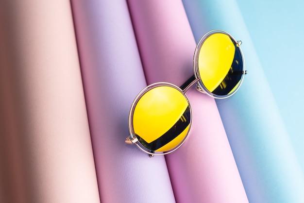 Moda de gafas de sol con lente amarilla puesta sobre fondo de papel de colores