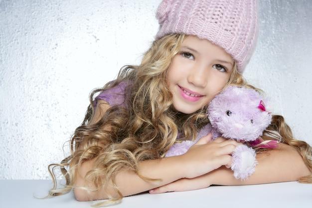 Moda de invierno tapa niña abrazo oso de peluche sonriendo