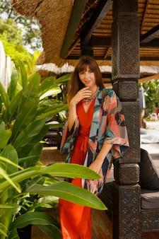 Moda isleña mujer elegante seductora en ropa de verano bohemia posando en resort de lujo tropical. concepto de vacaciones.