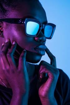 Moda joven africana mujer mujer usar anteojos mirando a la cámara aislada en el espacio de neón
