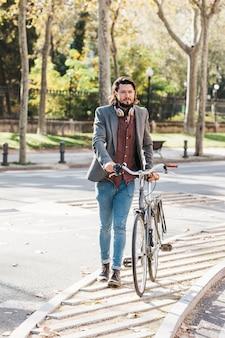 Moda joven con auriculares alrededor de su cuello caminando con su bicicleta en la acera