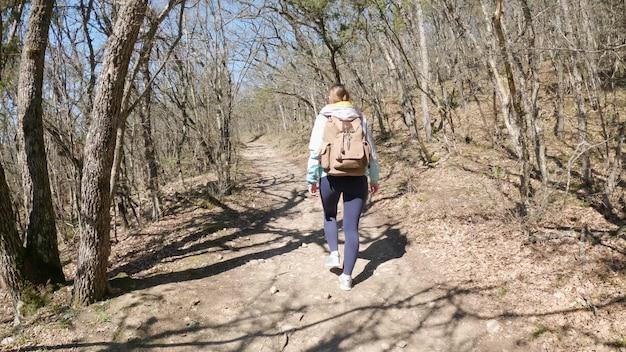 Moda joven caminando por el sendero del sendero del bosque de verano. viaje de niña en jeans y zapatillas de deporte. estilo de vida activo. concepto de senderismo, parque, aventura. cerca de las piernas femeninas. resistencia