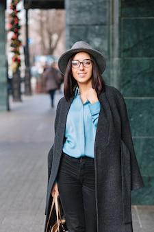 Moda joven empresaria alegre en gafas negras caminando por la calle en la gran ciudad. camisa azul, abrigo gris, sombrero, ropa de lujo, look elegante, sonrisas a los lados, verdaderas emociones.