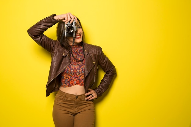 Moda joven hace la foto con cámara antigua en pared amarilla