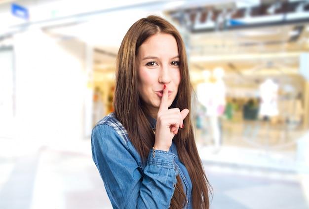 Moda joven mujer haciendo el gesto de silencio